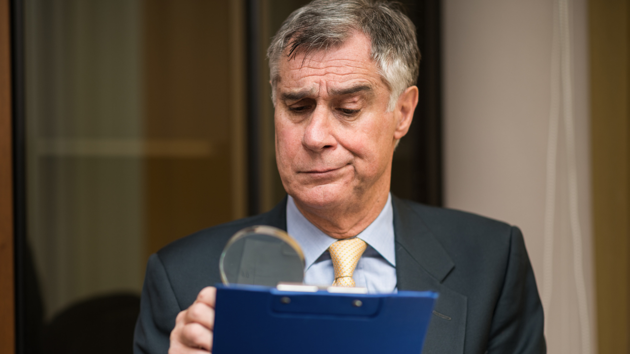 man suspiciously looking at clipboard with magnifying glass and smirk