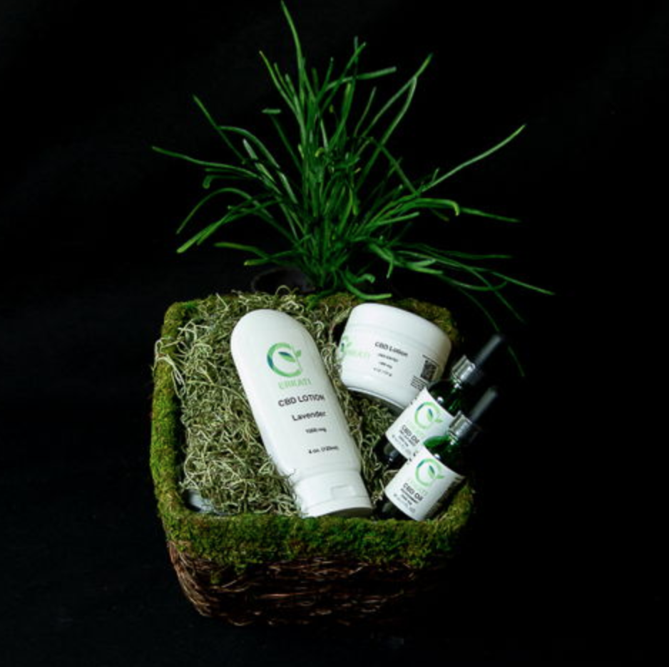 Two bottles of Erkati CBD Oil and Two bottles of Ekati CBD lotion in a gift basket on black backgound
